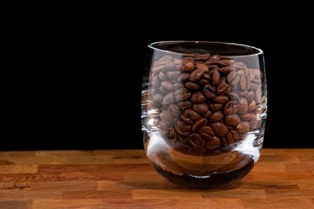 caf: coffea beans in glass on wooden table, black background