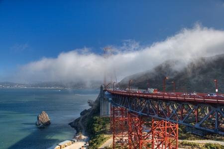 enveloping: A cloud enveloping the Golden Gate bridge in San Francisco