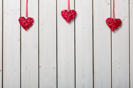 ladies day: Red hearts on white wooden background
