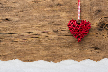 cordially: Red heart in front of wooden background with snow Stock Photo
