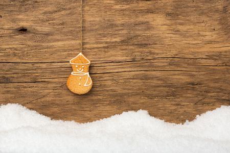 holz: Hängender Lebkuchen mit Schnee auf Holz