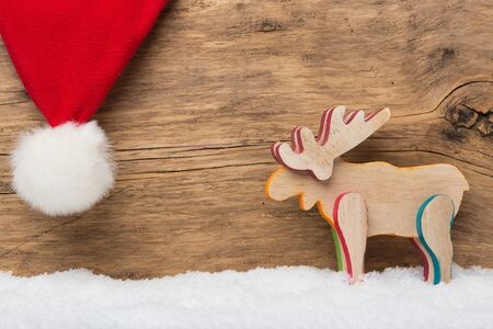 santa moose: Moose and santa hat on wooden background with snow