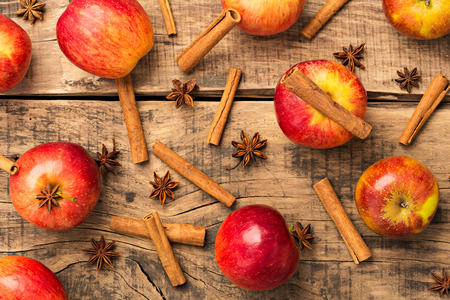 Red apples with wooden background and cinnamon
