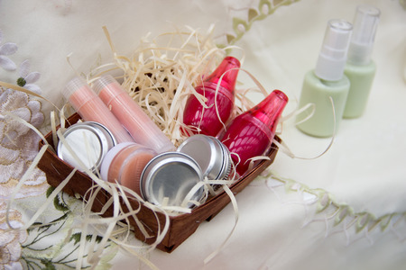 Four jars of cream, two lipsticks, two lip balm in a bright jar in a basket of bast are on the tablecloth.