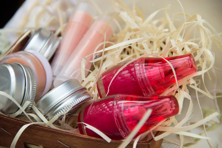 Two jars with bright lip balm, four jars of cream and two lipsticks in a basket of bast closeup are on the tablecloth. Stock Photo