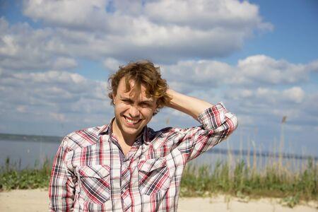 Man in plaid shirt laughs his head bowed.