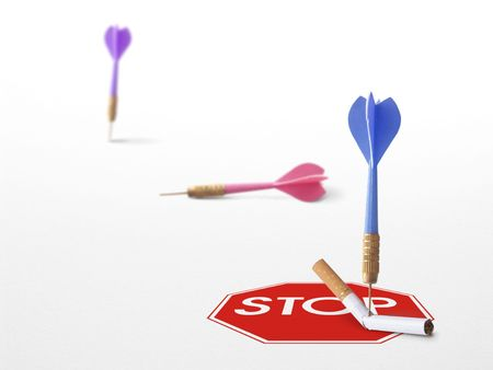 removing the risk: stop sign with a cigarette and a 3 darts on a white background