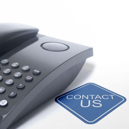 Téléphone noir isolé sur un fond blanc avec une courte phrase nous contacter  Banque d'images