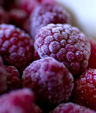 defrost: frozen fruits - fresh Raspberries in the freezer, vertical picture Stock Photo