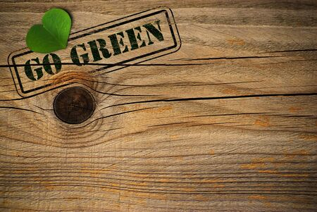 environment friendly: wooden background with green natural heart and go grren message