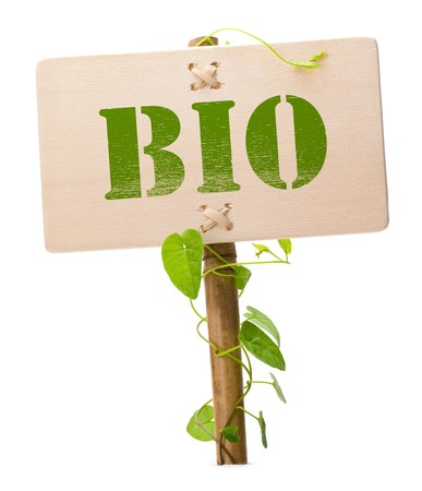 bio sign message on a wooden panel and green plant - image is isolated on a white background photo
