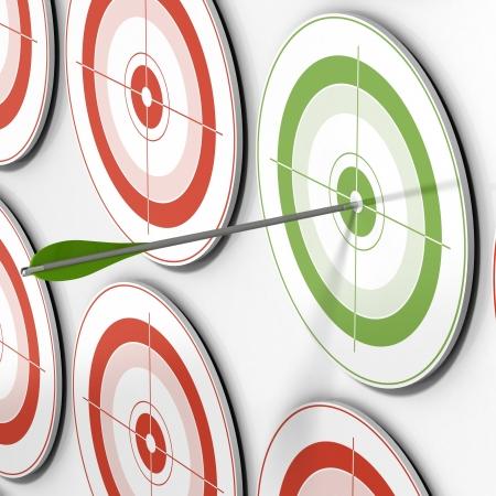 objetivo: uno de los objetivos verde y una flecha al golpear el centro y muchos destinos rojos  Foto de archivo