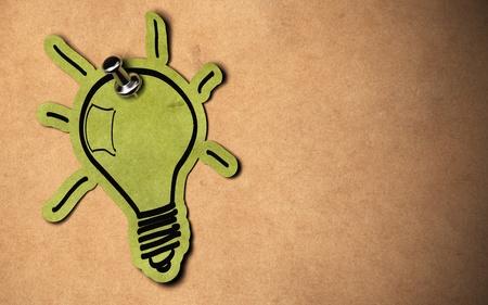 clavados: concepto de bombilla verde, bulbo de papel fijada sobre un fondo de papel kraft con espacio de copia Foto de archivo
