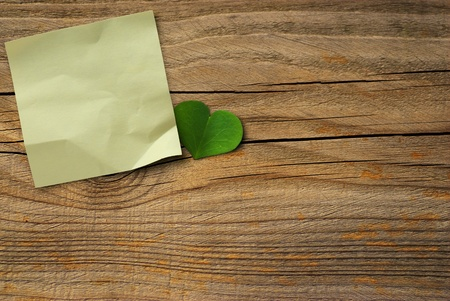 yellow note paper and green clover petal over a wooden wall, horizontal image photo