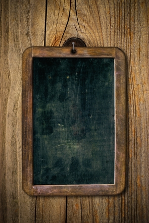 dirty and scratched wooden school slate over a wood wall, vertical image photo