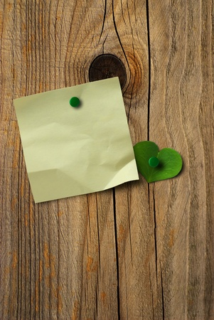 yellow note paper and green clover petal over a wooden wall, vertical image photo