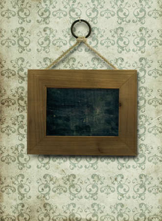 fixed: empty wooden frame fixed on a old and dirty wall, the inner part of the frame is a slate, the wallpaper is stained and dirty with arabesques on it, the frame is fixed by a nail ans a rope