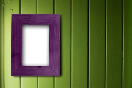 simple frame: empty purple frame fixed on a green wooden wall, the color of the inner part of the frame is white