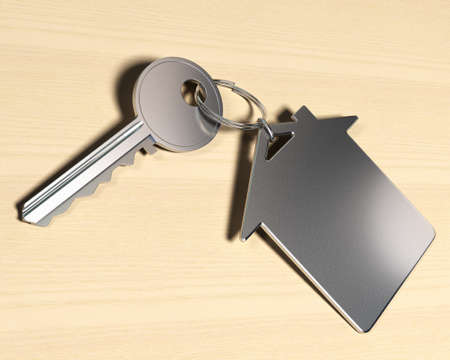 keyring: house symbol keyring and a key over a wooden background, real-este symbol  Stock Photo