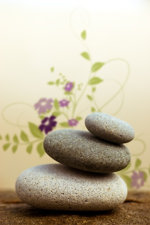 stacked up: pebbles pyramid on a rock with floral design at the background - beige background Stock Photo