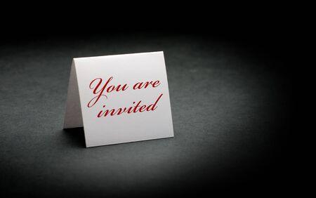 te negro: est�n invitados escrito en rojo en un signo de blanco. imagen es sobre un fondo de papel negro