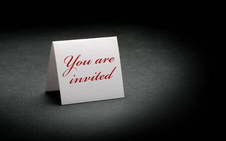 invited: you are invited written in red on a white sign. image is over a black paper background