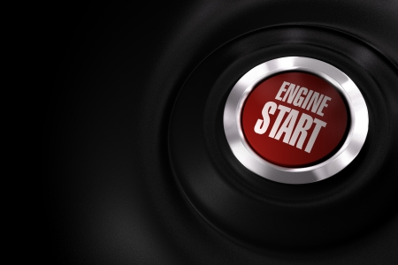 red engine start button over a black background with copy space on the left side of the image photo