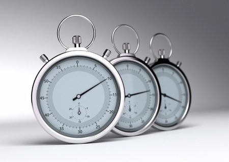 analogs: three stopwatches over a grey background with blur