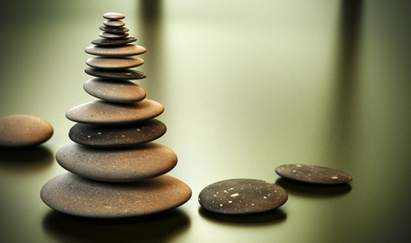 perfection: Tall pebble stack over a yellow green background with room for text on the right side