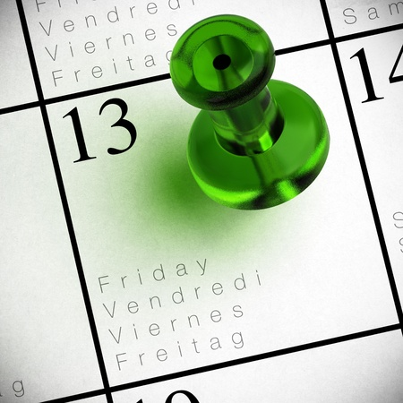 superstition: friday the 13th written onto a multilingual calendar with a red thumbtack with transparency Stock Photo