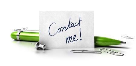 Neem contact met mij met de hand geschreven op een wit visitekaartje, groene balpen, punaise en paperclips op een witte achtergrond met bezinning Stockfoto