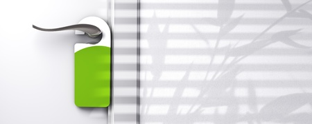 green blank plastic door hanger fixed onto a knob, wall with free space, room for text, shadow of a plant, real estate or hotel communication concept photo
