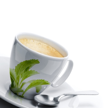 sweetener: cup of coffee decorated with stevia rebaudiana leaves, plus a spoon  White background border of a page, left angle