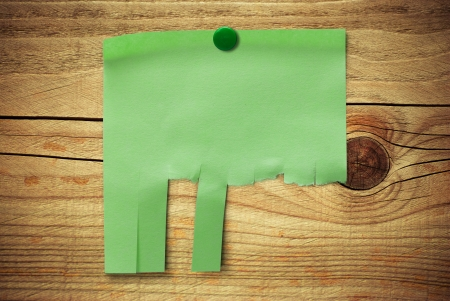 blank green note with tearable strips over wooden background, can be customized to enter some text, address and contact details   photo