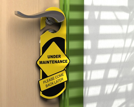 web page under construction: yellow and black hanger where it is written under maintenance please come back later hanged onto a door handle, concept for a website page under construction Stock Photo