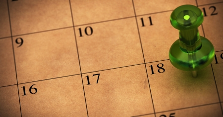 18: Green thumbtack onto a schedule made with recycled brown paper  Pushpin pointed on number 18  Appointment on a calendar, room for text on the left side of the memo Stock Photo