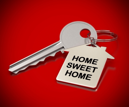 home sweet home: home sweet home written onto a metal keyring, home shape  metallic key over red background Stock Photo
