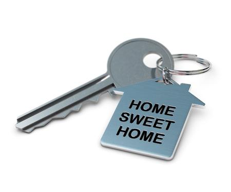 keyring: home sweet home written onto a metal keyring, home shape  metallic key over white background