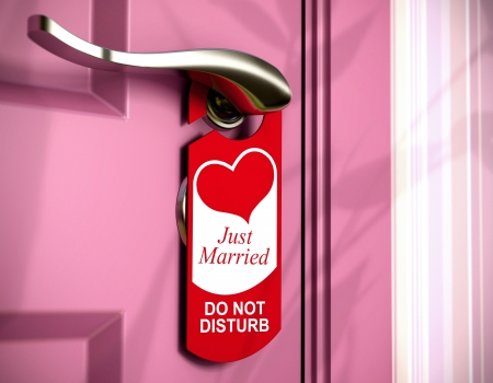 just married: just married written onto a red door hanger, hanged on a metal handle of a pink bedroom door, concept of honeymoon  Stock Photo