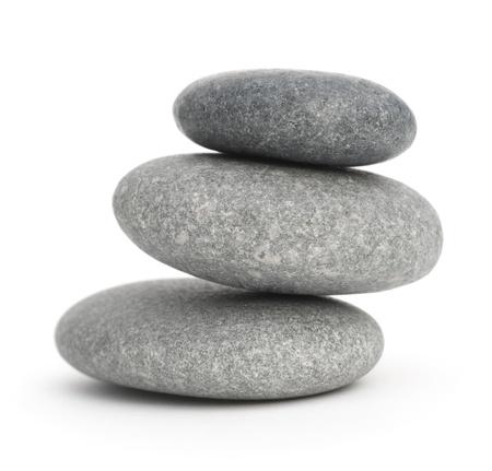 drie kiezelstenen gestapeld op elkaar, 3 stenen op een witte achtergrond Stockfoto