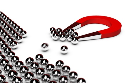 magnets: red horseshoe magnet attracting some chrome balls from a crowd, white background