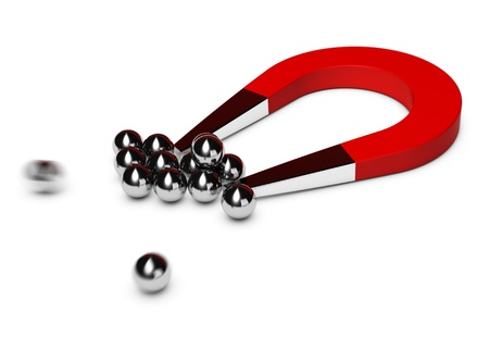 magnets: red horseshoe magnet attracting some chrome balls, white background Stock Photo