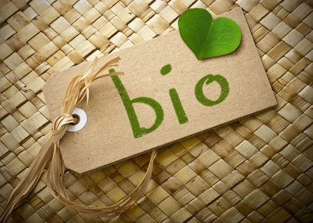 Natual cardboard label with the word bio handwritten on it plus a green clover petal  photo