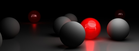 be: one red ball illuminating many grey sphares over a black background, symbol of difference Stock Photo