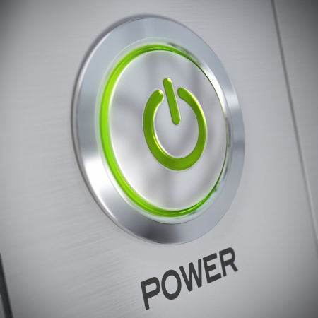 power button on a brushed aluminum panel with a green light and the symbol of energy start, blur effect photo