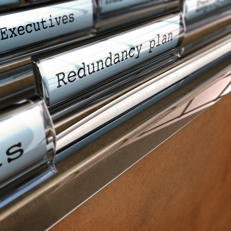 restructuring: redundancy plan written on a folder with the word executives at the background, perspective view and blur effect Stock Photo