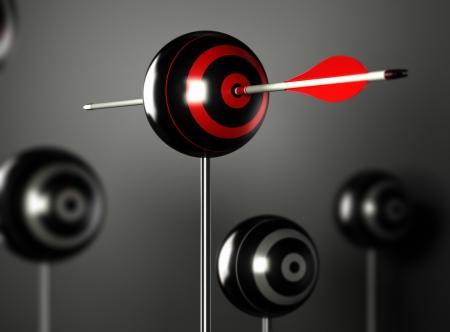 commitment: una flecha roja golpeando el centro de una diana pelota con otros objetivos de la falta de definici�n alrededor, fondo negro con efecto de luz Foto de archivo