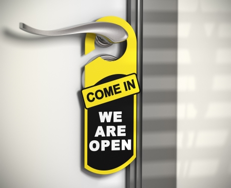 come in: door hanger with the message come in we are open hanged on a door handle. Stock Photo