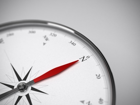 precise: Measure instrument, compass with red needle pointing to the north  Blur effect focus on the letter N  Grey background