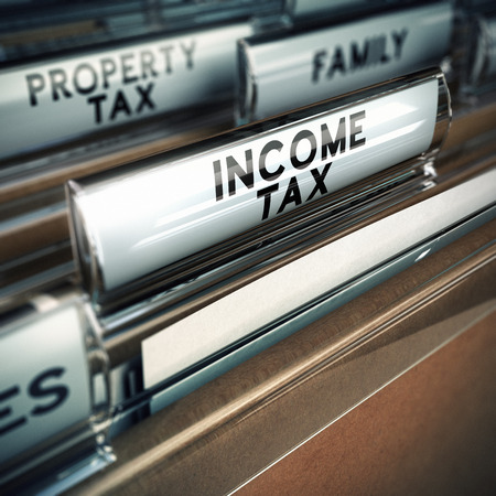 taxable income: files with close up and focus on the income tax tab, blur effect  Conceptual image suitable for taxes illustration